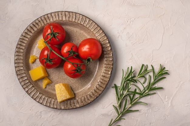 Cherry tomatoes, parmesan cheese on a ceramic plate and rosemary twig on light textured background