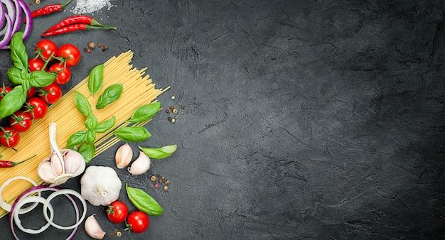 ミニトマト、パスタ、バジル、ニンニク、タマネギ、唐辛子、胡椒、黒いコンクリートのテーブル、パスタを作るための材料