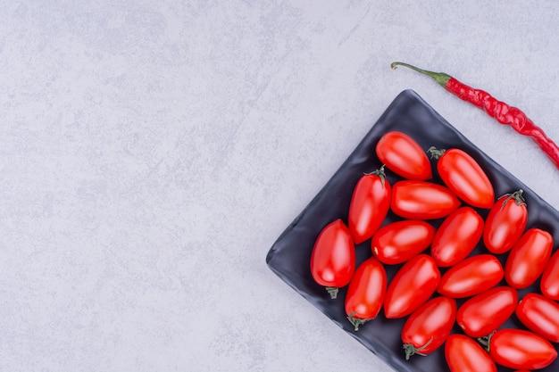 Pomodorini e peperoncino rosso in un piatto di ceramica