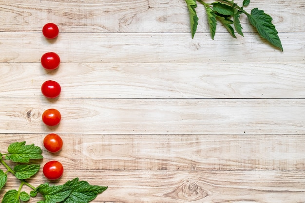 Cherry tomatoes in a row with leaves on light  wooden table background with copy space