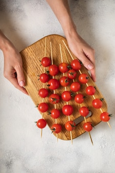 Cherry tomatoes on swords holding by hands