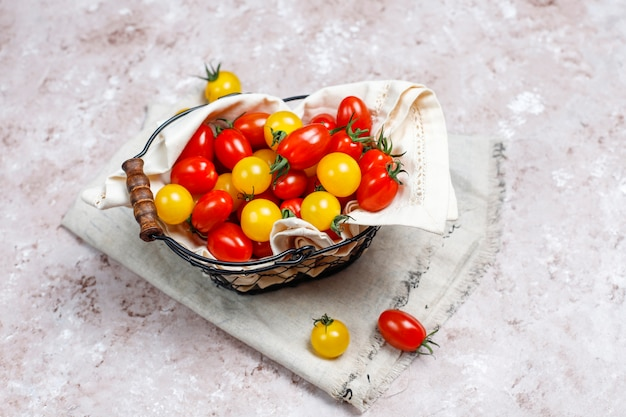 Cherry tomatoes of various colors,yellow and red cherry tomatoes in a basket on light background
