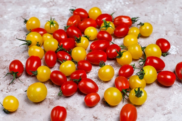 Cherry tomatoes of various colors,yellow and red cherry tomatoes on light background