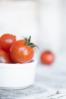 Cherry tomatoes in white ceramic bowl on white wood
