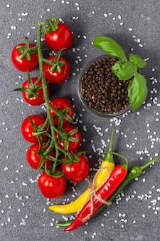 Помидоры черри с базиликом, душистым перцем, острым перцем чили и солью на сером фоне. вид сверху свежих овощей.