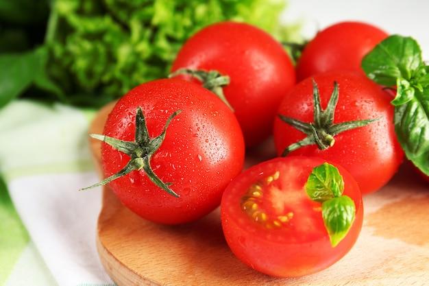 나무 테이블에 바 질 체리 토마토를 닫습니다.