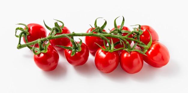 흰색 바탕에 복사 공간이 있는 체리 토마토. 신선한 야채의 측면 보기입니다.