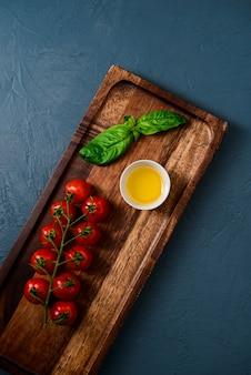 青い表面上の木の板に油でチェリートマト