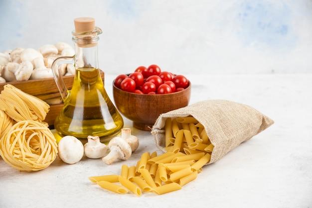 Pomodorini con olio d'oliva, funghi e pasta cruda sul marmo.