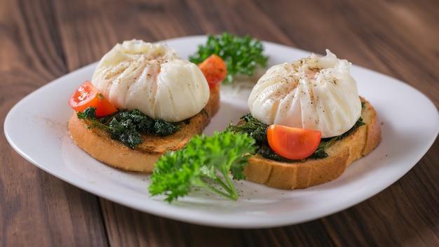 木製のテーブルの上のパンにポーチドエッグとチェリートマト。ポーチドエッグとベジタリアンスナック。