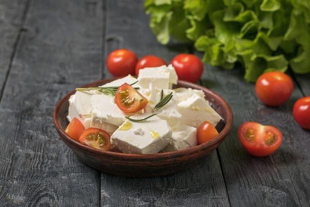 테이블에 죽은 태아의 치즈 조각이 있는 체리 토마토. 치즈와 야채 샐러드.