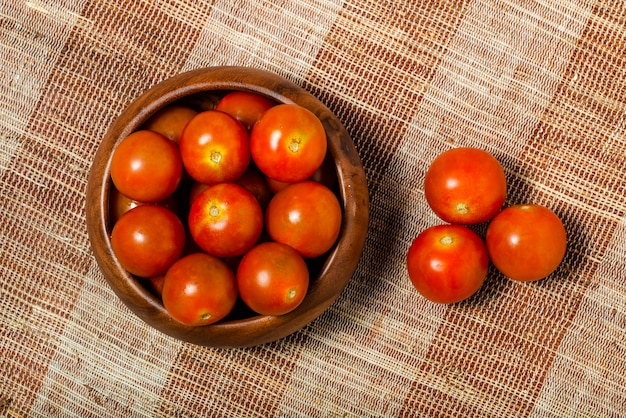 Cherry tomatoes in a wooden bowl on a fabric texture background. top view. macro photography