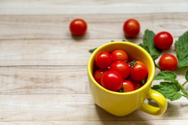 Cherry tomatoes in a yellow cup and green leaves on light wooden table background