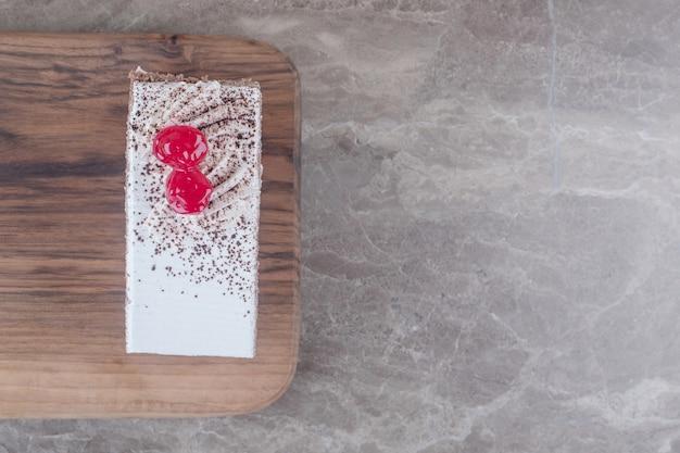 Fetta di torta ricoperta di ciliegie su una tavola su marmo