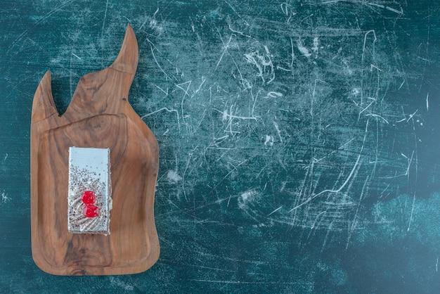 青い背景の上の木の板に桜のトッピングケーキスライス。高品質の写真