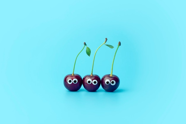 青色の背景に目をした桜。子供のための面白い野菜や果物。離乳食のコンセプト、食品の顔。