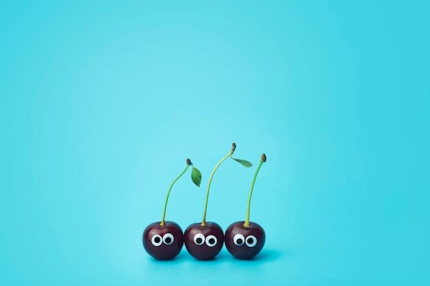 Вишня с глазами на синем фоне. веселые овощи и фрукты для детей. концепция детского питания, питание лица.