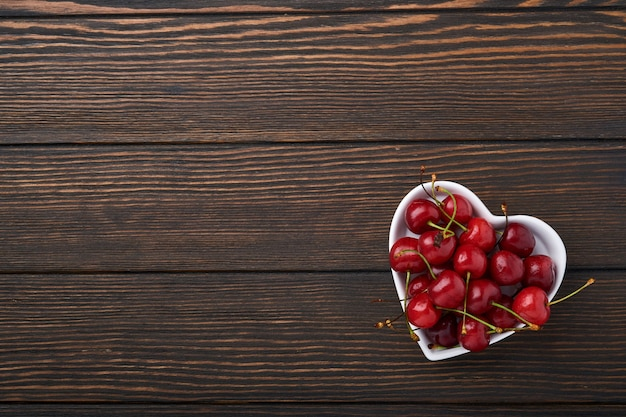 Cherry with water drops on heart shaped plate on dark brown stone table. fresh ripe cherries. sweet red cherries. top view. rustic style. fruit background