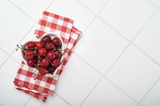 Вишня с каплями воды на тарелке в форме сердца на белом каменном столе. свежие спелые вишни. черешня красная. вид сверху. деревенский стиль. фруктовый фон