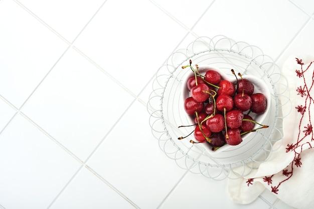 白い石のテーブルの上のハート型のプレートに水滴と桜。新鮮な熟したサクランボ。甘い赤いサクランボ。上面図。素朴なスタイル。果物の背景