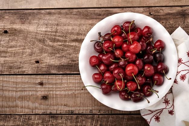 ダークブラウンの石のテーブルの上の白いボウルに水滴と桜。新鮮な熟したサクランボ。甘い赤いサクランボ。上面図。素朴なスタイル。果物の背景