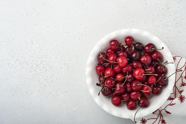 Вишня с каплями воды на белом шаре на белом каменном столе. свежие спелые вишни. черешня красная. вид сверху. деревенский стиль. фруктовый фон