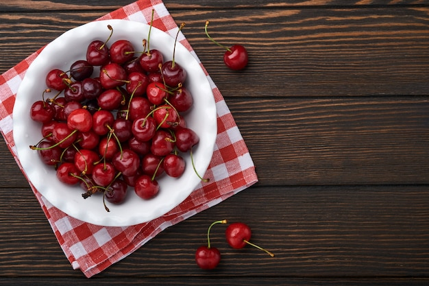 Cherry with water drops on white bowl on dark brown stone table. fresh ripe cherries. sweet red cherries. top view. rustic style. fruit background