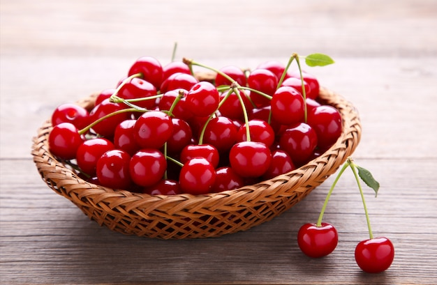Cherry in wooden basket with leaves on grey table.
