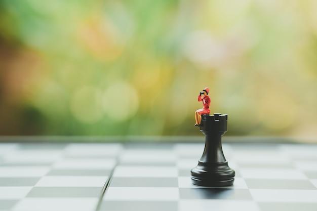 Chess analysisの上に座っているミニチュアのビジネスマンビジネスについてコミュニケーション