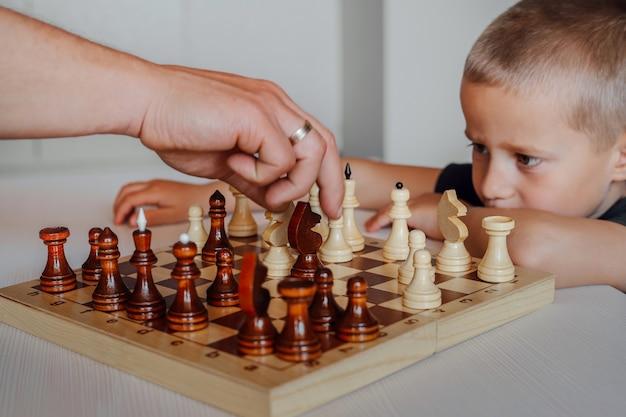Крупный план шахматной доски, на которой играют отец и сын партии. маленький белый мальчик внимательно следит за рукой своего отца.