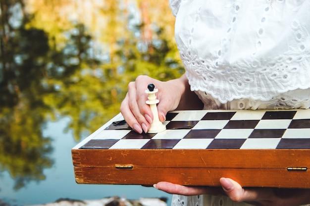 Шахматная доска. девушка играет в шахматы. белая фигура короля в шахматах.