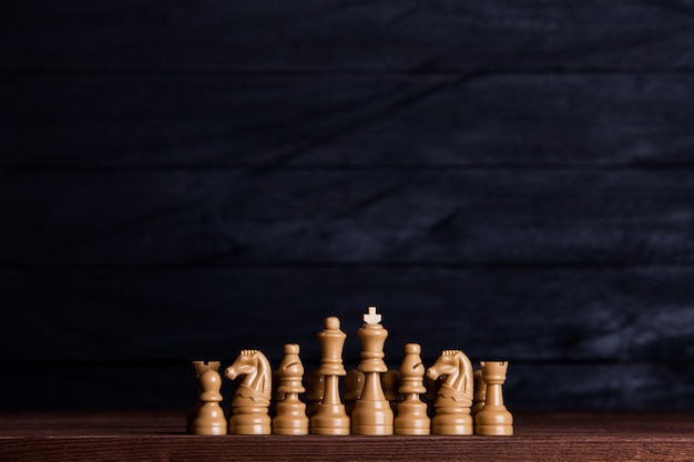 Chess board with chess pieces over dark background