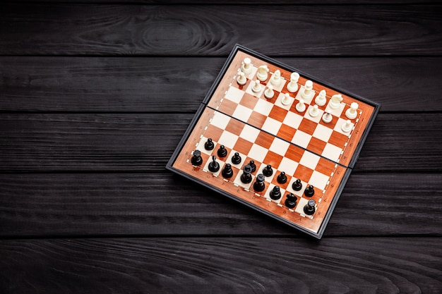 Chess board with chess pieces on it on black table