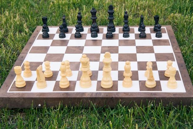 緑の芝生の上のチェスの駒とチェス盤。白い部分に選択的に焦点を当てます。アウトドアチェスゲーム