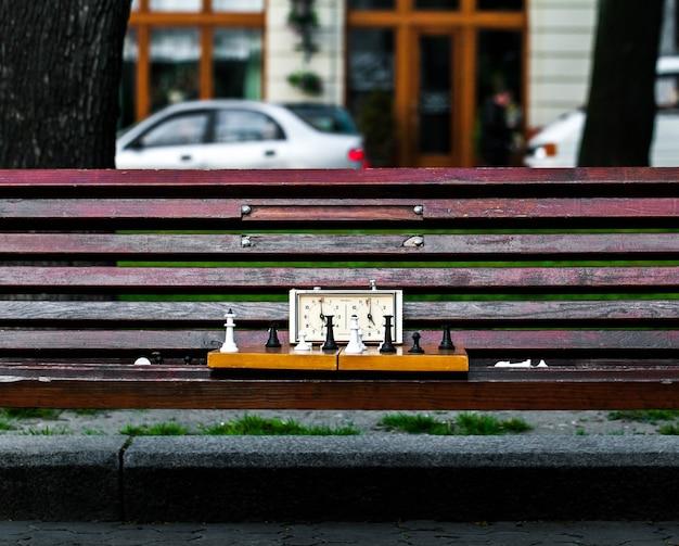 木製のベンチにチェスの駒が付いたチェス盤。木製のチェスの駒を使った屋外チェスゲーム