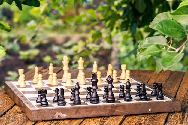 リンゴの木の枝と背景に緑の葉が付いている木製の机の上のチェスの駒とチェス盤。黒い部分に選択的に焦点を合わせる