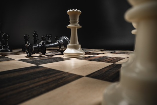 Chess board with figures on dark background macro