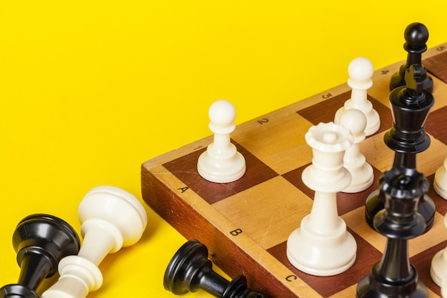 Chess board with figures on yellow background top view copy space