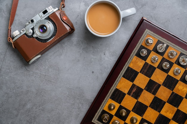 Шахматная доска с кусочками, кофе и камерой
