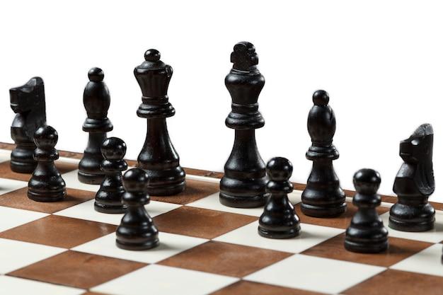 白い背景で隔離の木片とチェス盤