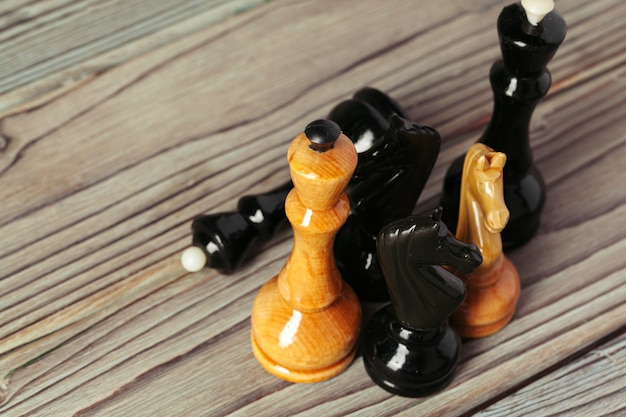 Chess figures on dark wooden background side view copy space