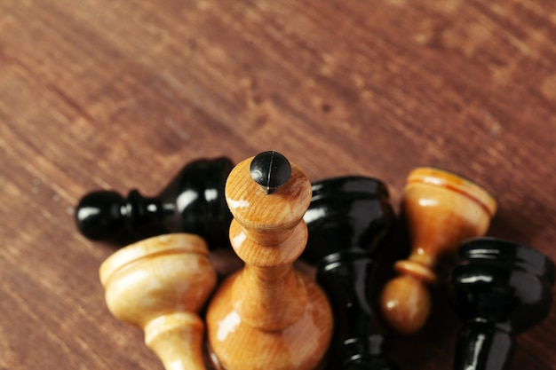 Chess figures on dark wooden table, side view copy space