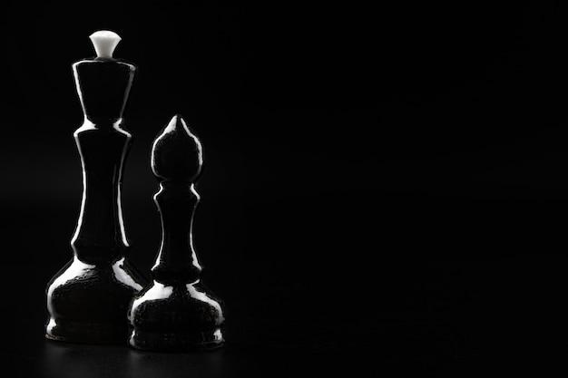 Шахматные фигуры на темно-черном фоне крупным планом фото