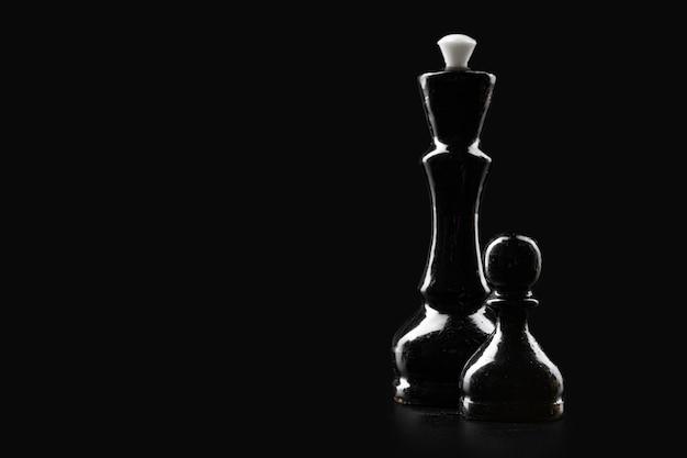 Шахматные фигуры на темном черном фоне крупным планом