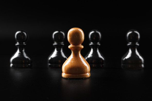 Шахматные фигуры на темно-черной поверхности крупным планом