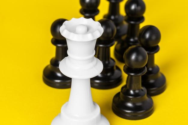 Шахматные фигуры на желтом вид сверху copyspace