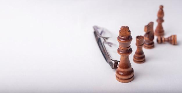 흰색 테이블에 eyeglasse와 체스 수치입니다.