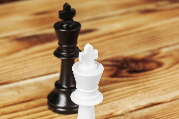 Chess figures on wooden background close up