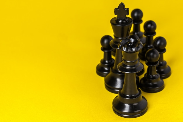 Chess figures on yellow background top view copy space