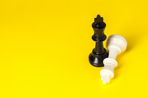Chess figures on yellow  top view copy space